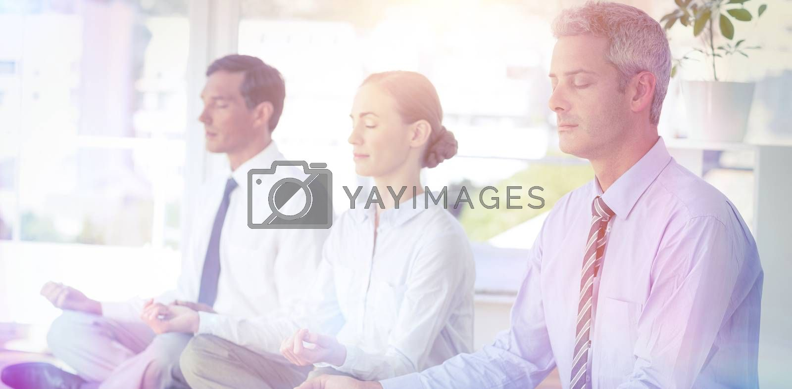 Business people doing yoga on floor in office