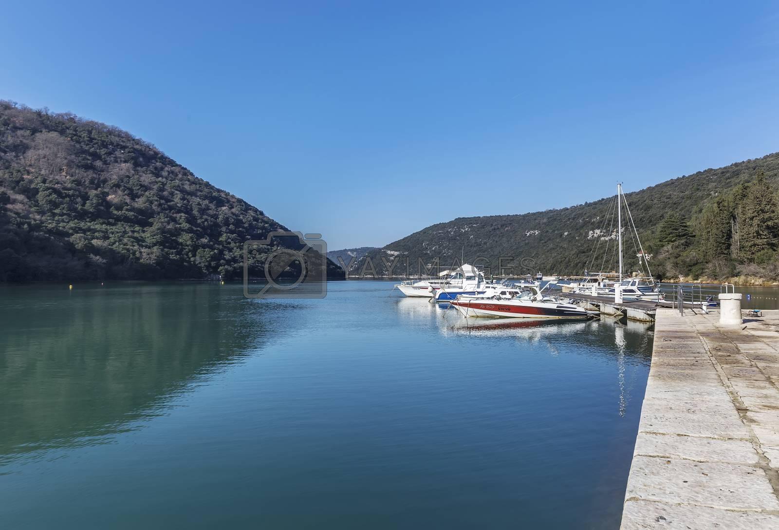 LIMSKI KANAL, CROATIA - January 29, 2020: Anchored boats in a sunny port in the Lim Canal, Istria, Croatia