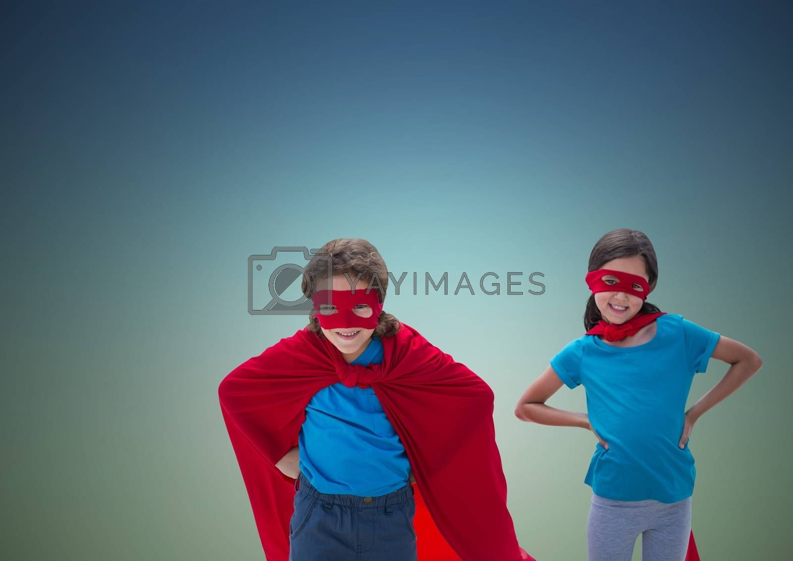 Two children wearing superhero costume standing with hands on hip against blue background