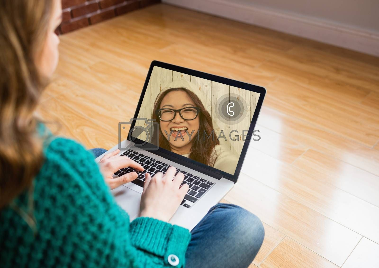 Woman sitting on wooden floor having a video chat with friend on laptop at home