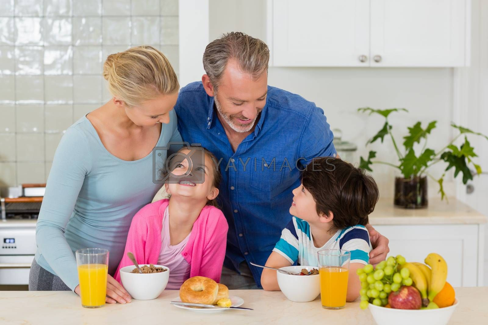 Happy family having breakfast in kitchen at home