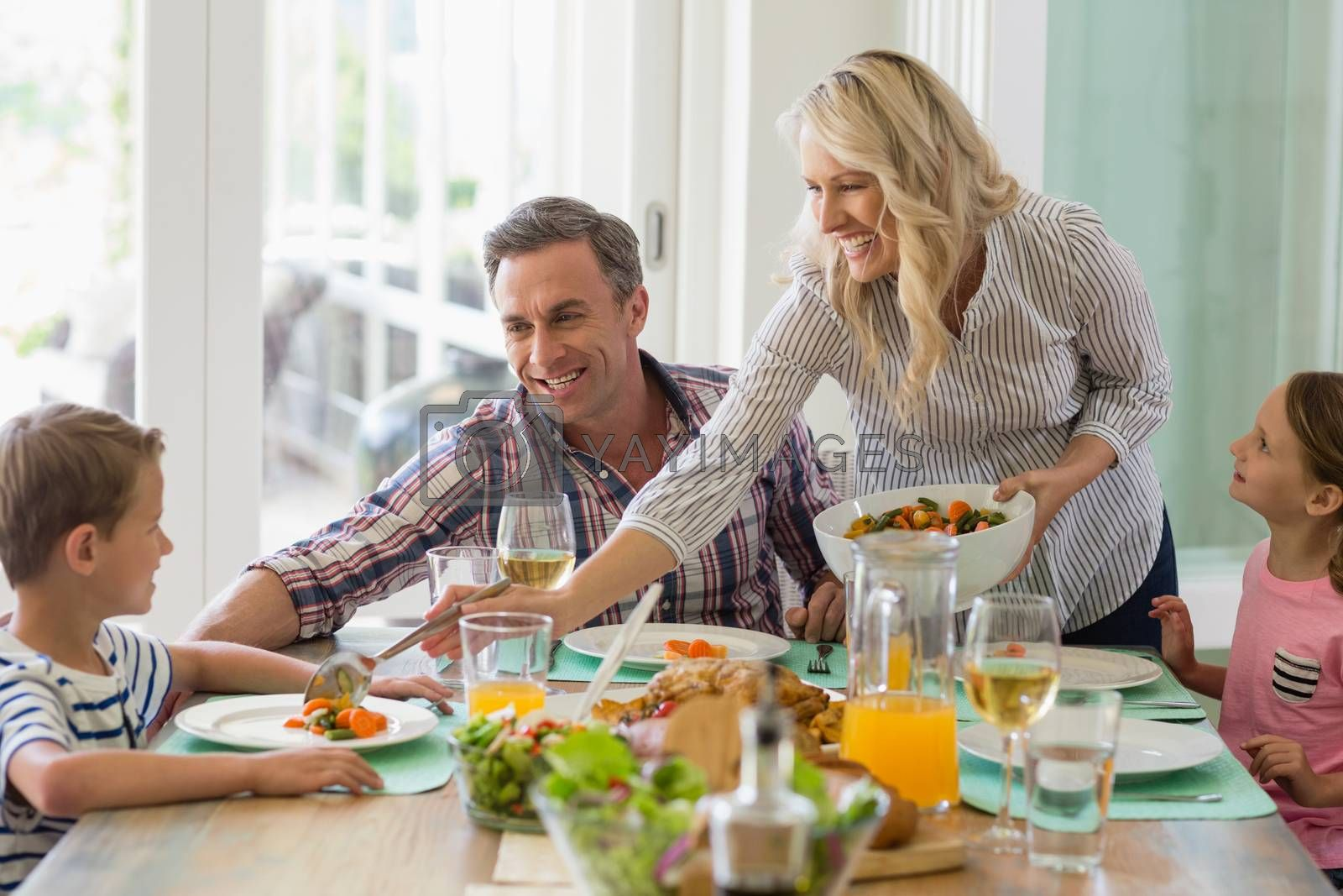 Mother serving food to family on dinning table at home