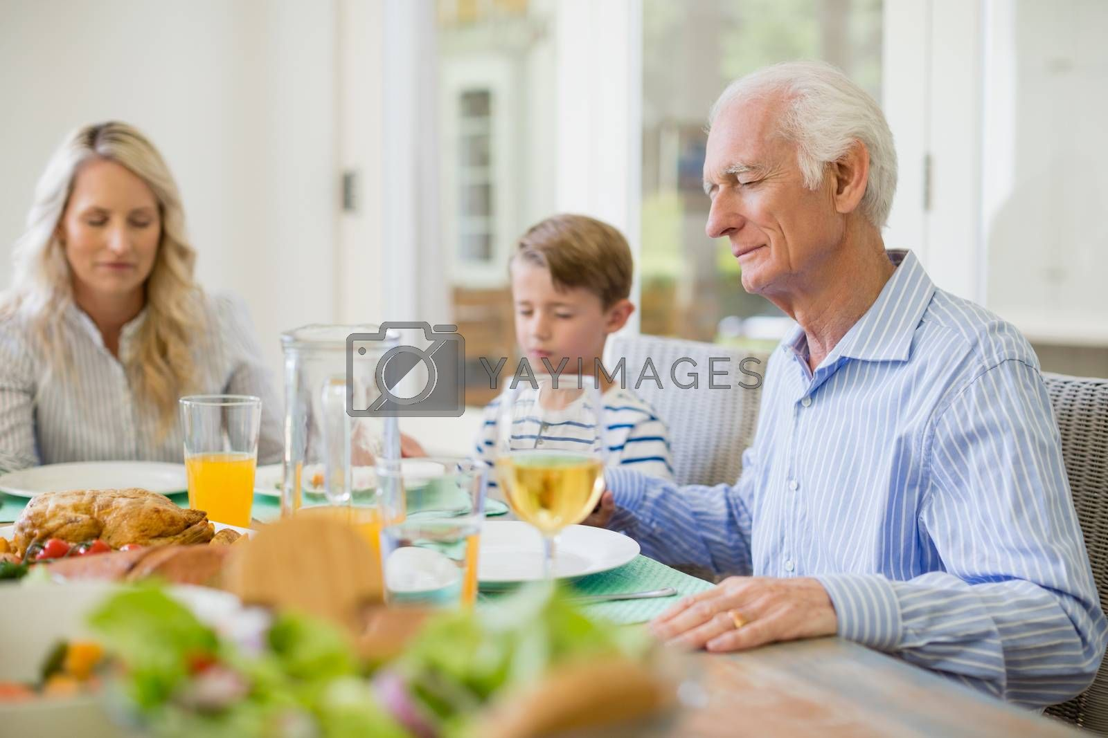 Multi-generation family praying before having meal by Wavebreakmedia