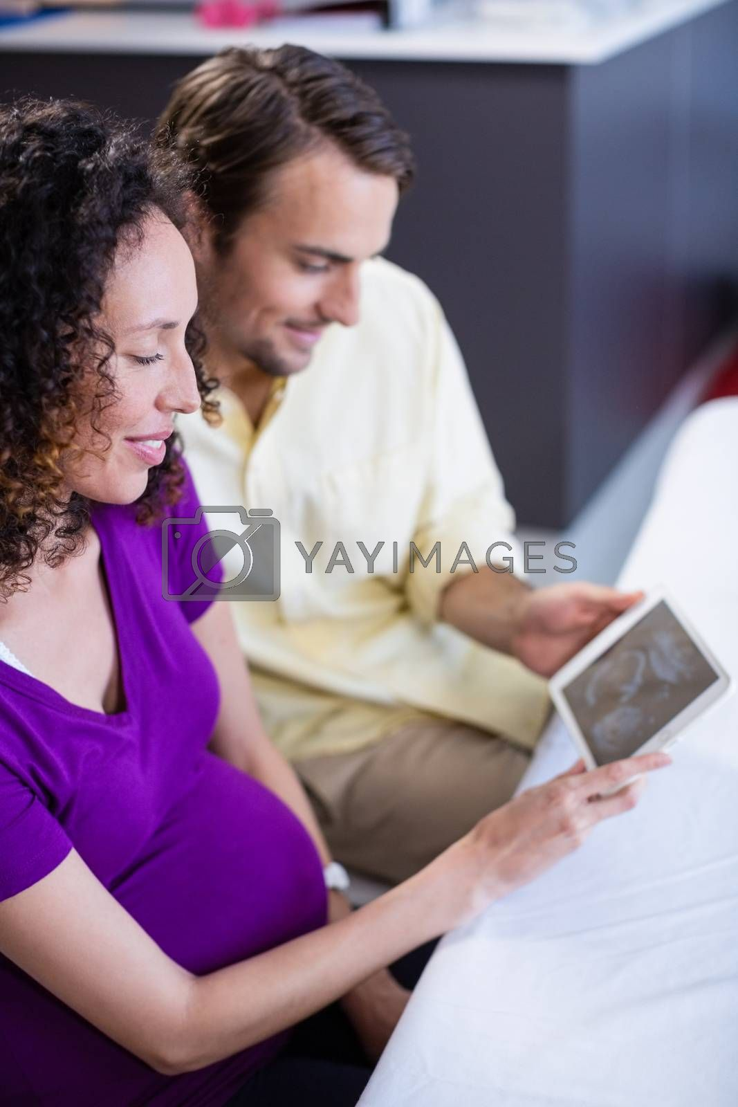 Couple looking at babies ultrasound scan on digital tablet in hospital
