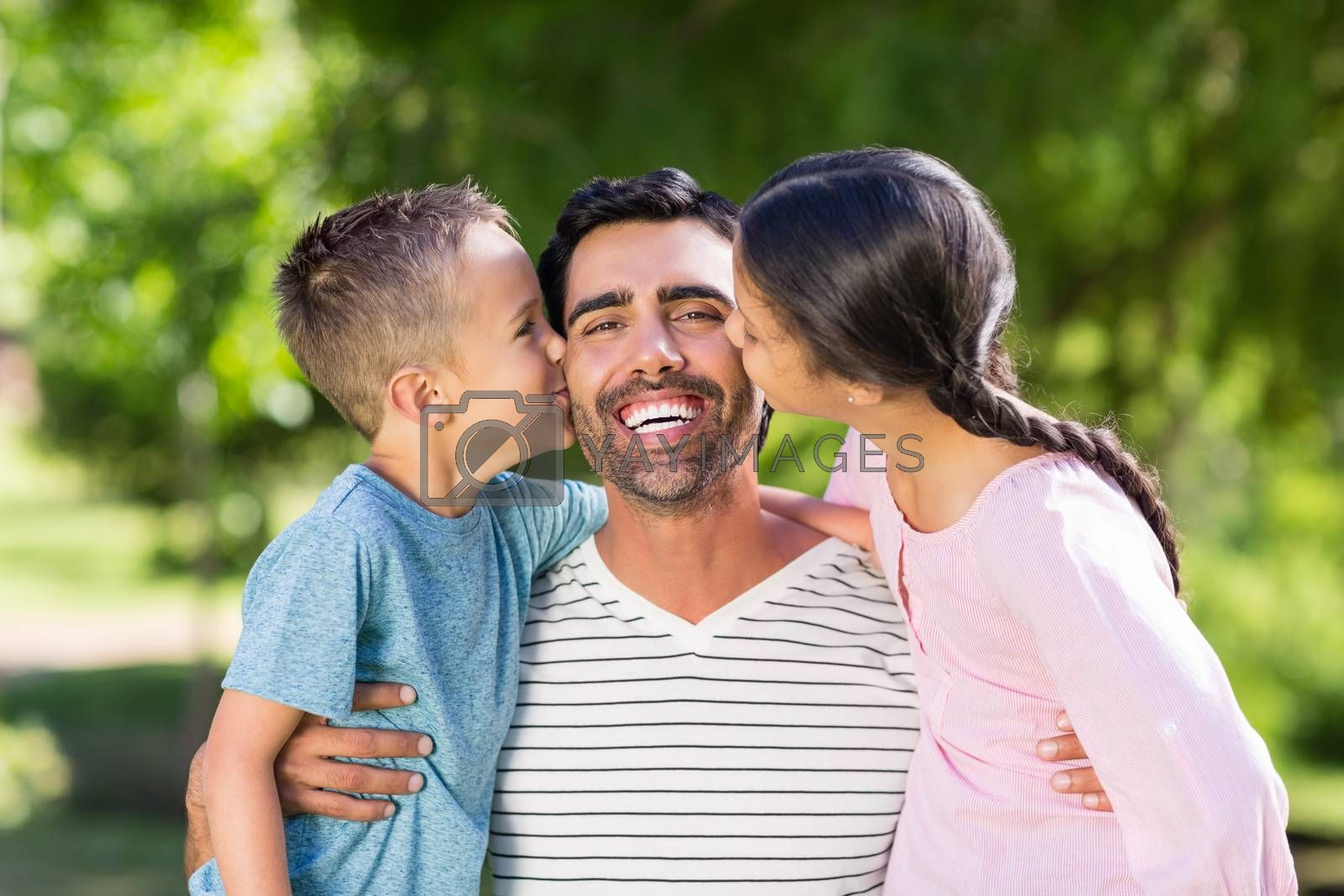 Father having fun with his son and daughter in park on a sunny day