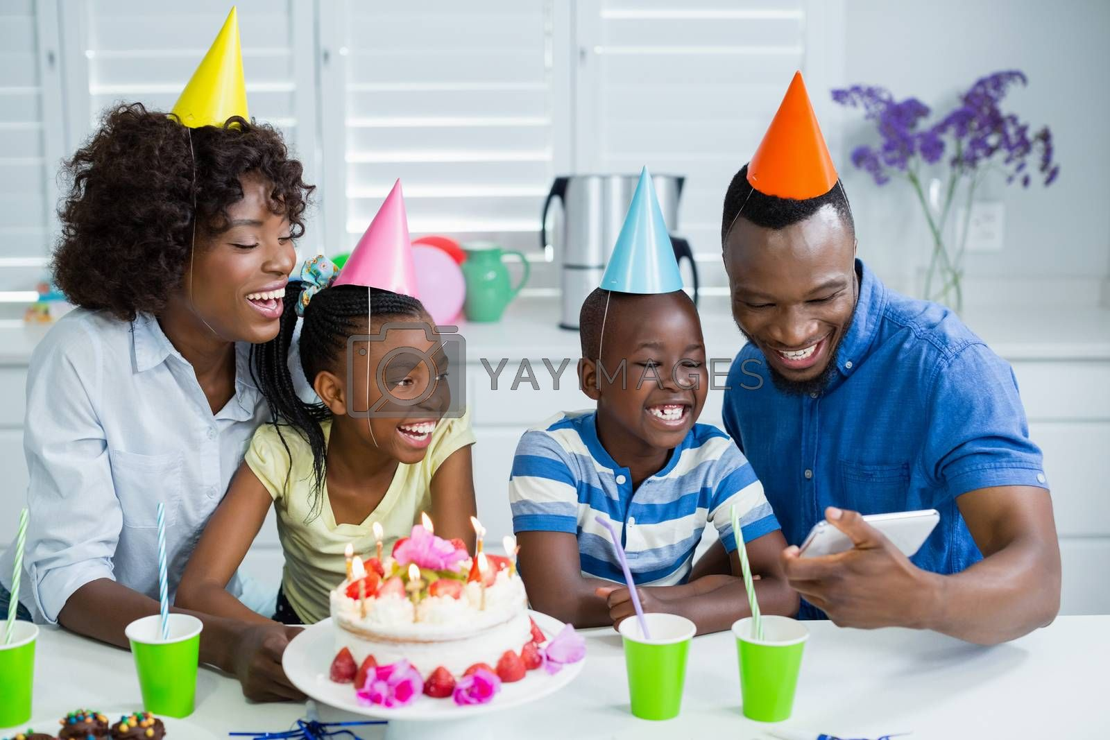 Family looking at picture while celebrating birthday party at home