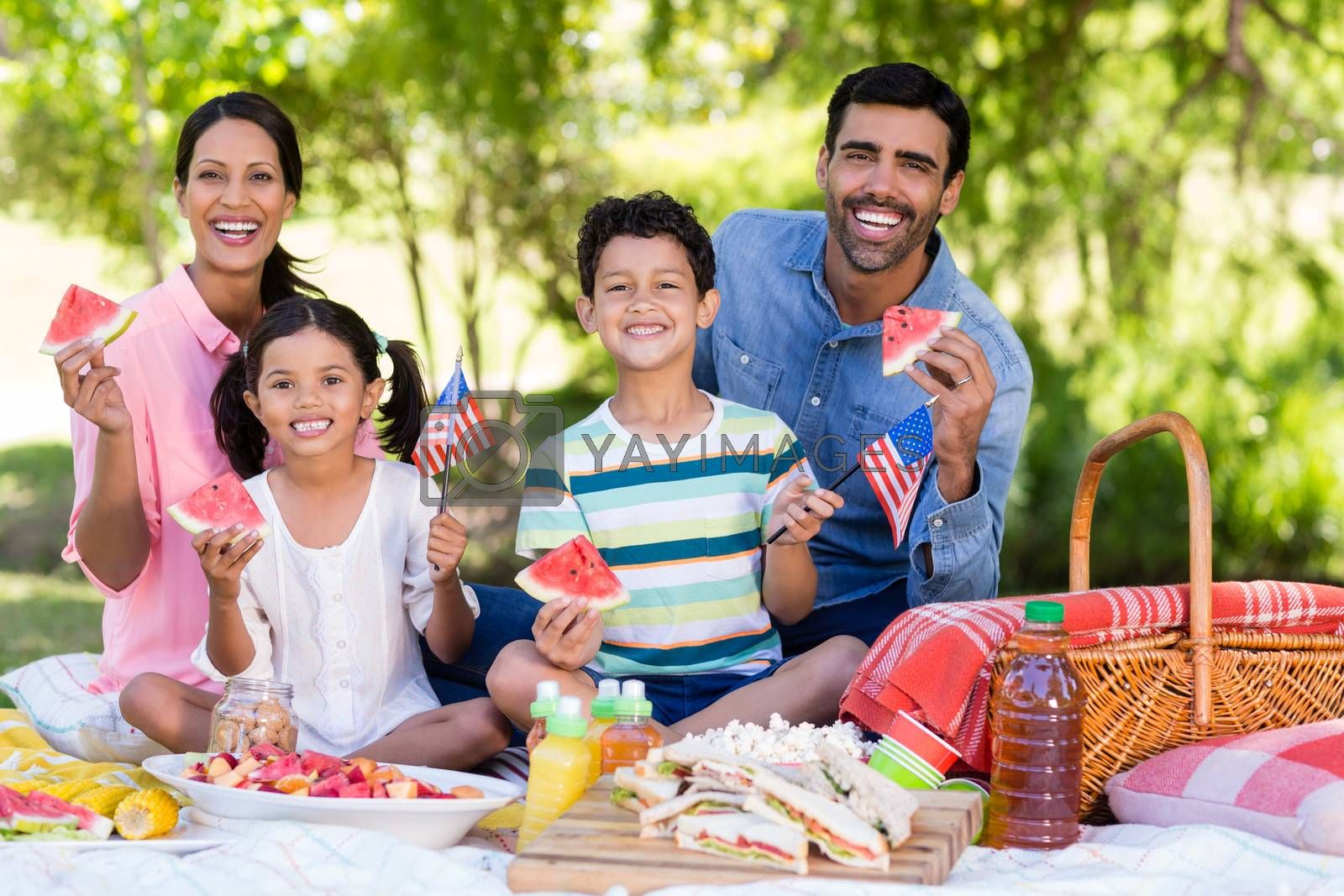 Portrait of family having breakfast in a park on a sunny day