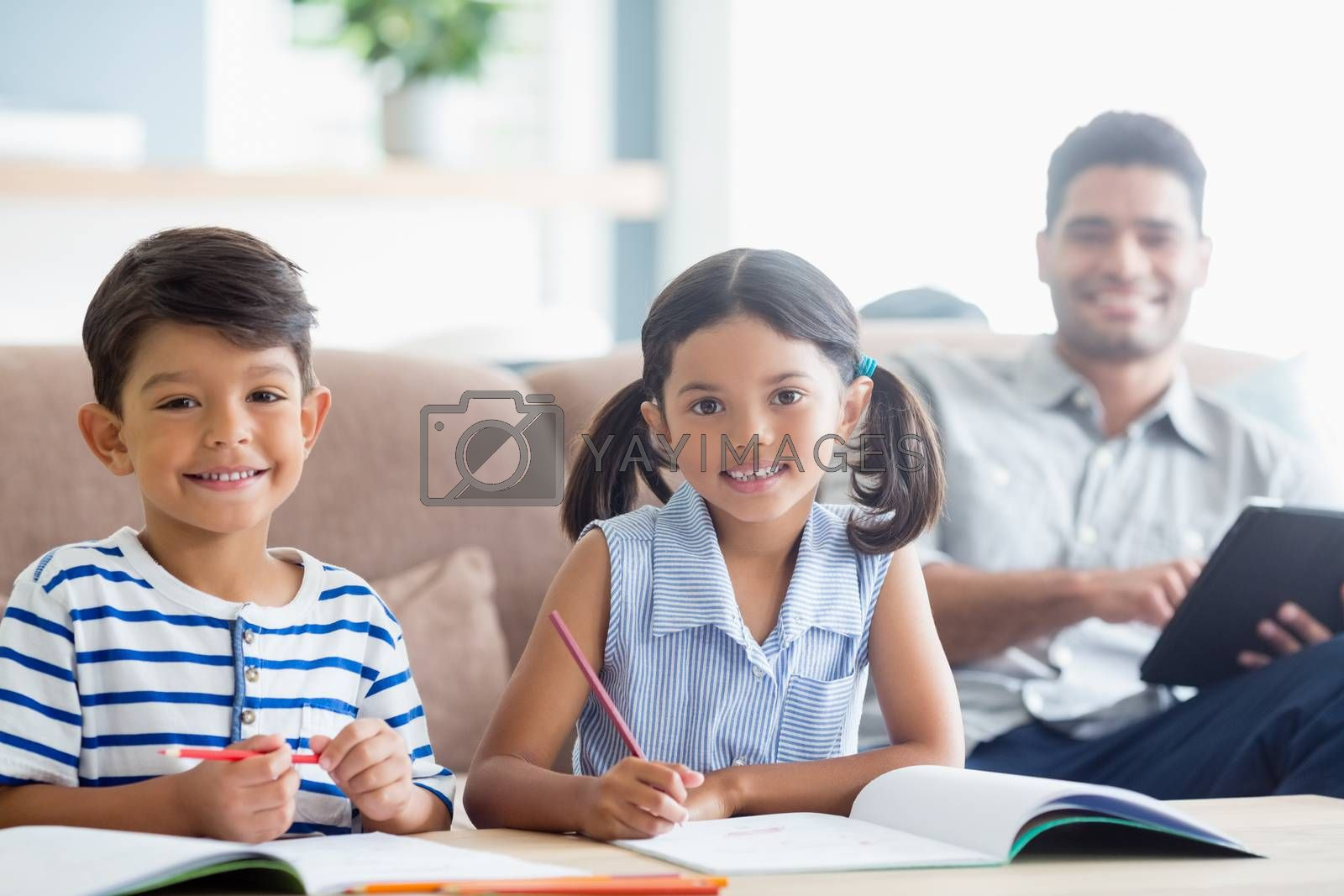 portrait of smiling siblings doing homework in living room at home