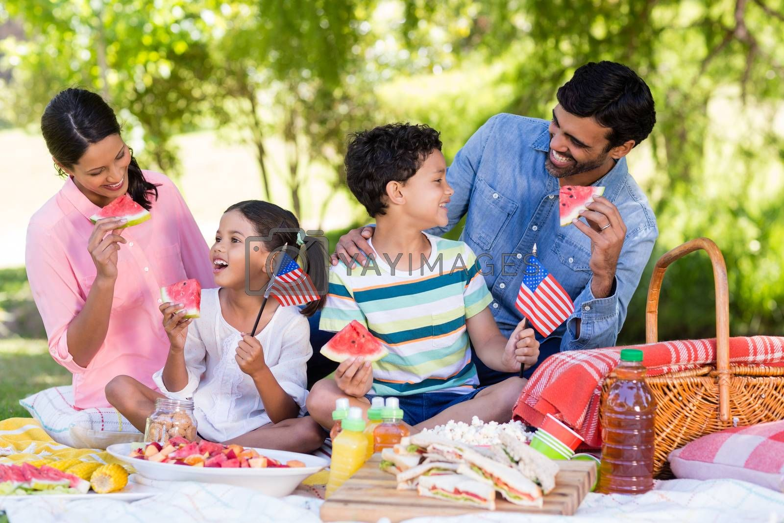 Happy family having breakfast in a park on a sunny day