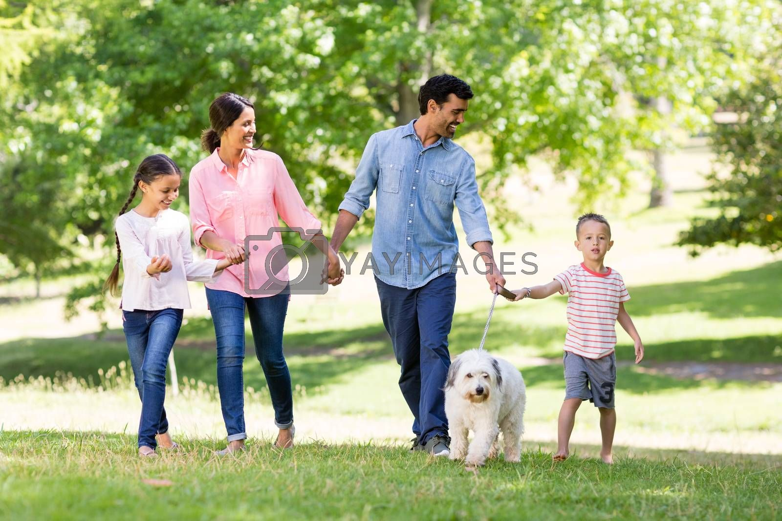 Happy family enjoying together with their pet dog in park