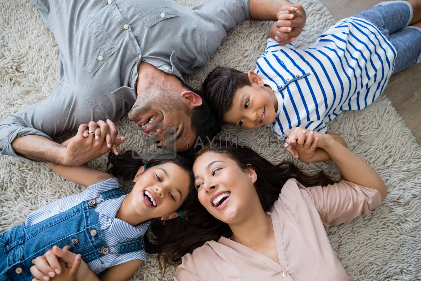 Happy family interacting while lying on rug at home