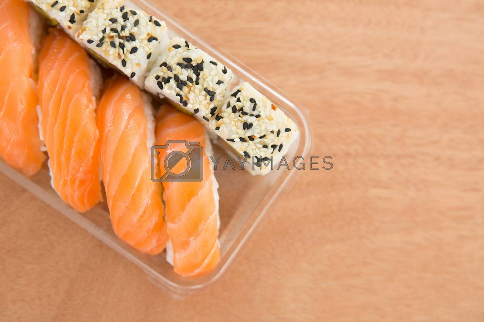 Sushi rolls with salmon in plastic container