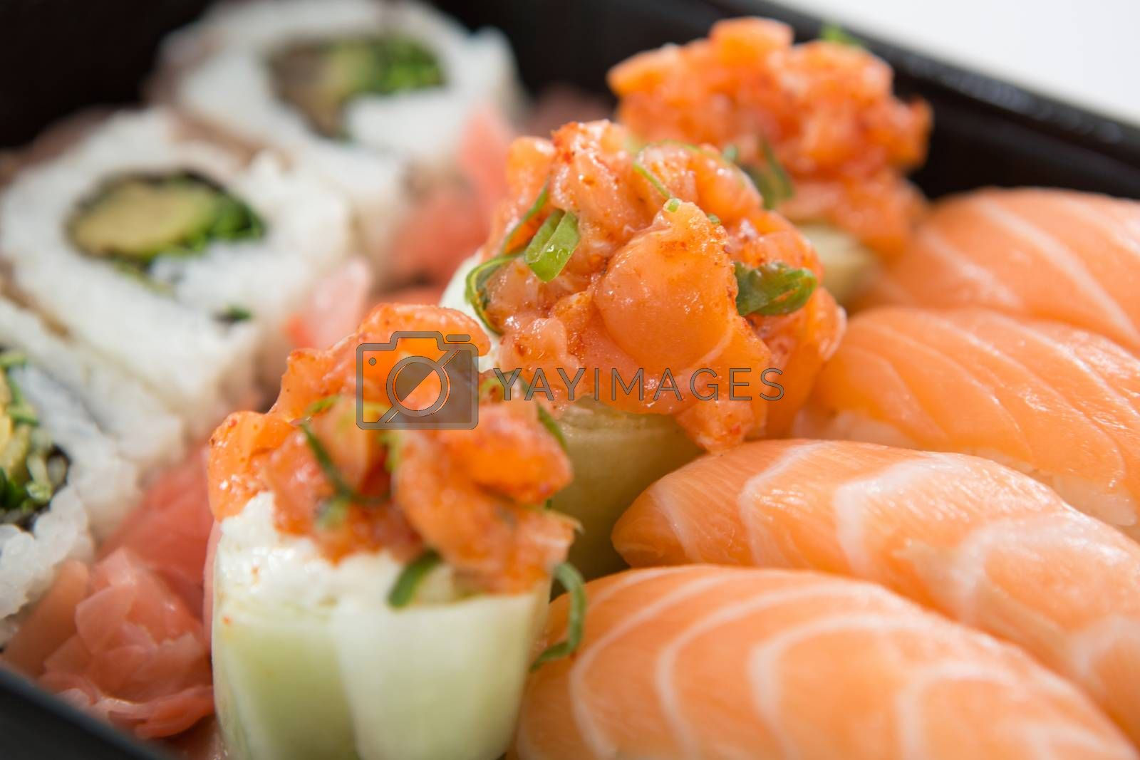 Tray of assorted sushi against white background