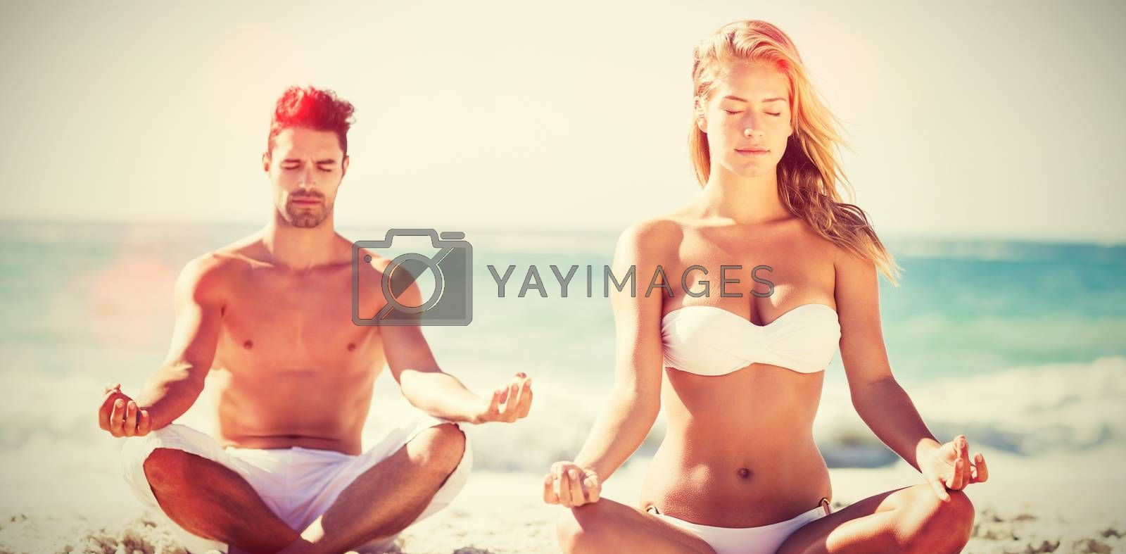 Happy couple doing yoga on beach during sunny day