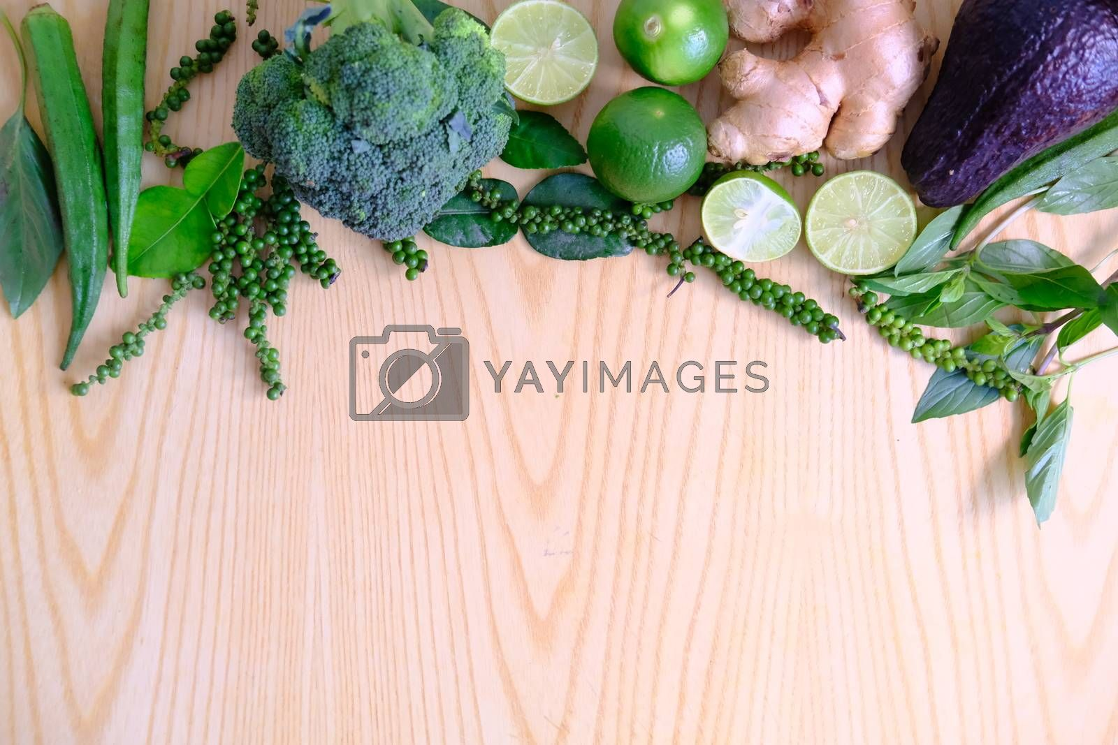 Fresh ripe green vegetables broccoli, ginger, lime, avocado, green pepper, Green okra and basil leaves on wooden background.  Organic vegetarian food ingredients vegetables  close up.