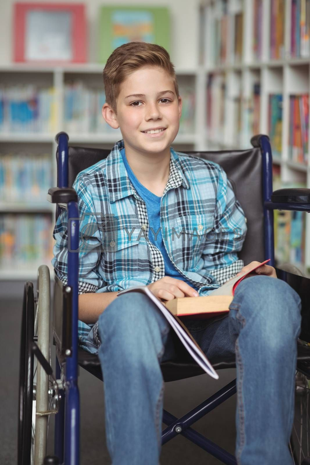 Portrait of disabled schoolboy holding book in library at school