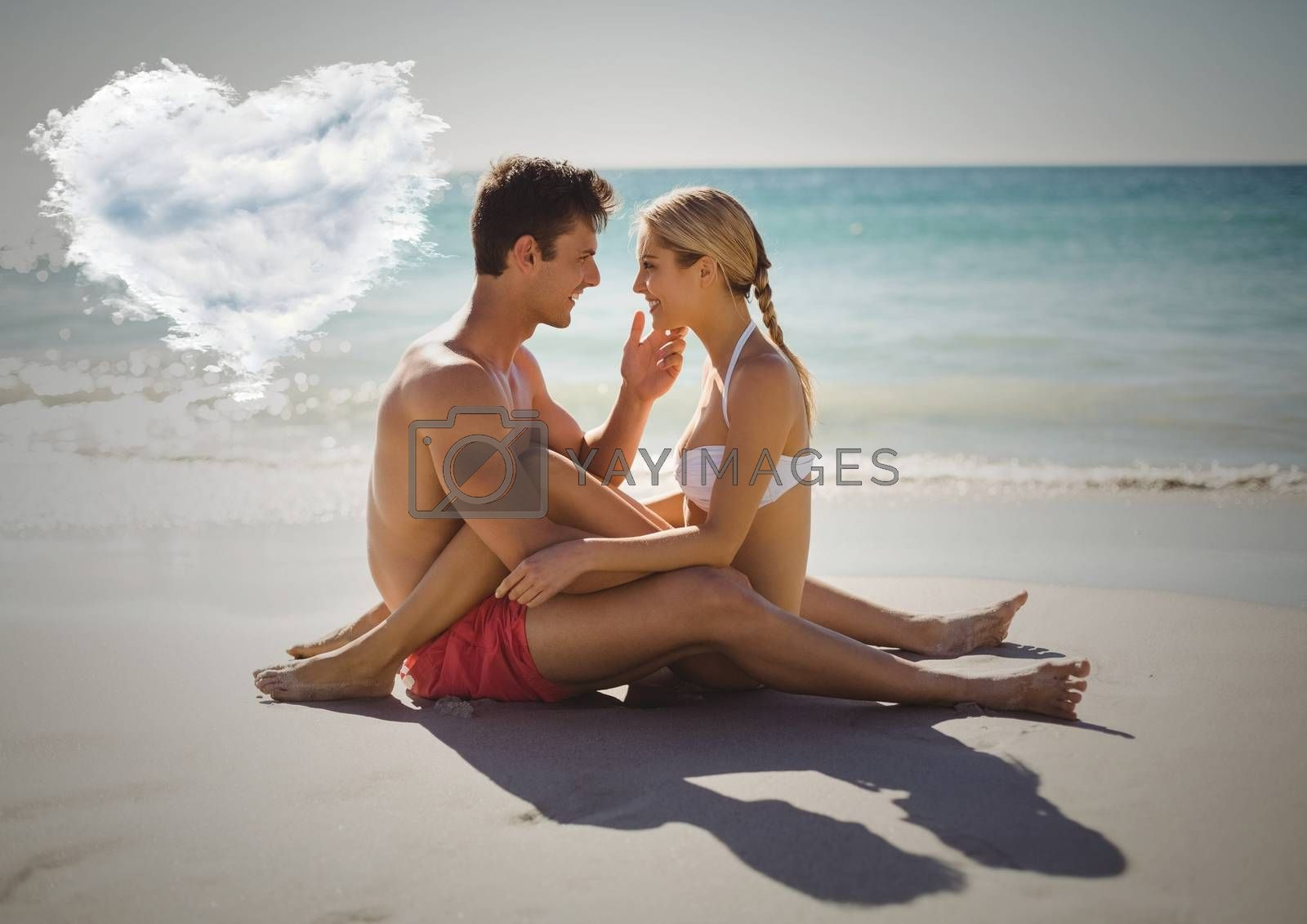 Composite images of romantic couple sitting on beach with heart cloud