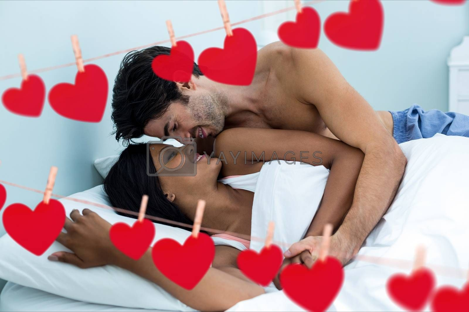 Composite image of red hanging hearts and young couple doing romance in bedroom at home