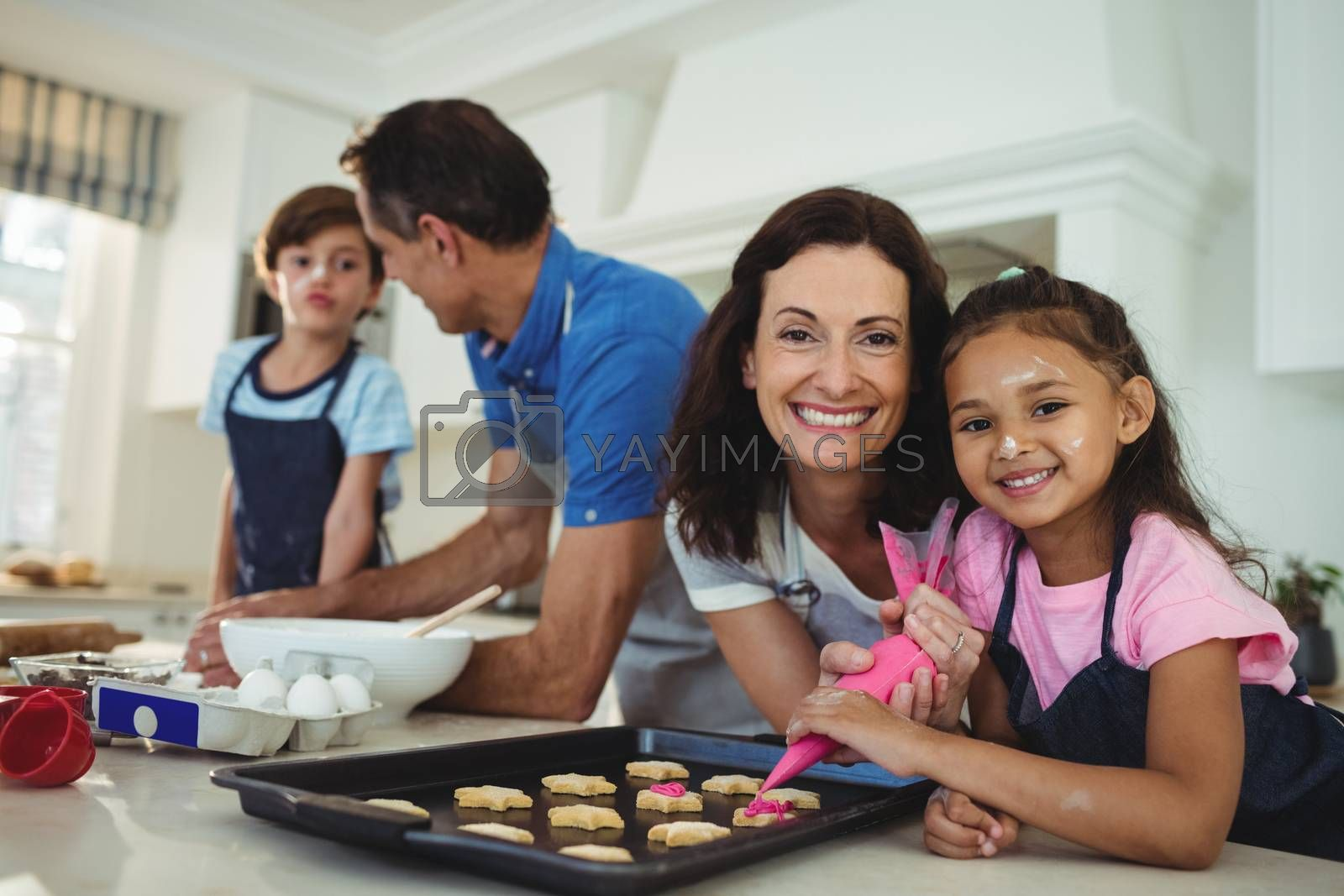 Happy family preparing cookies in kitchen at home