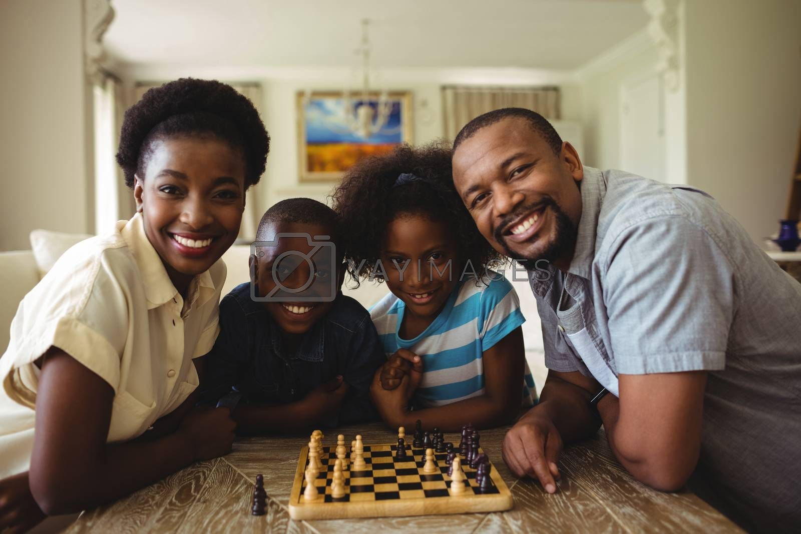 Portrait of family playing chess together at home in the living room at home