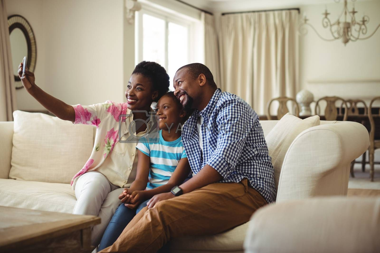 Family taking selfie on mobile phone in living room at home