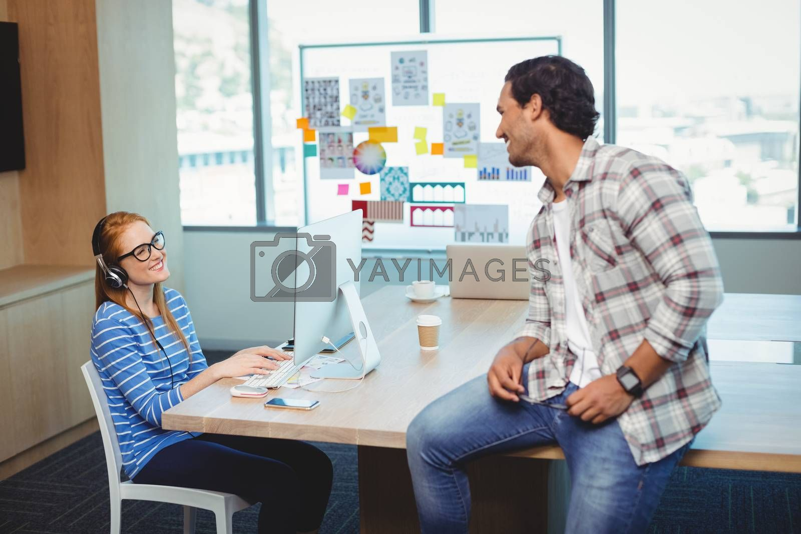 Graphic designers interacting with each other in conference room at office