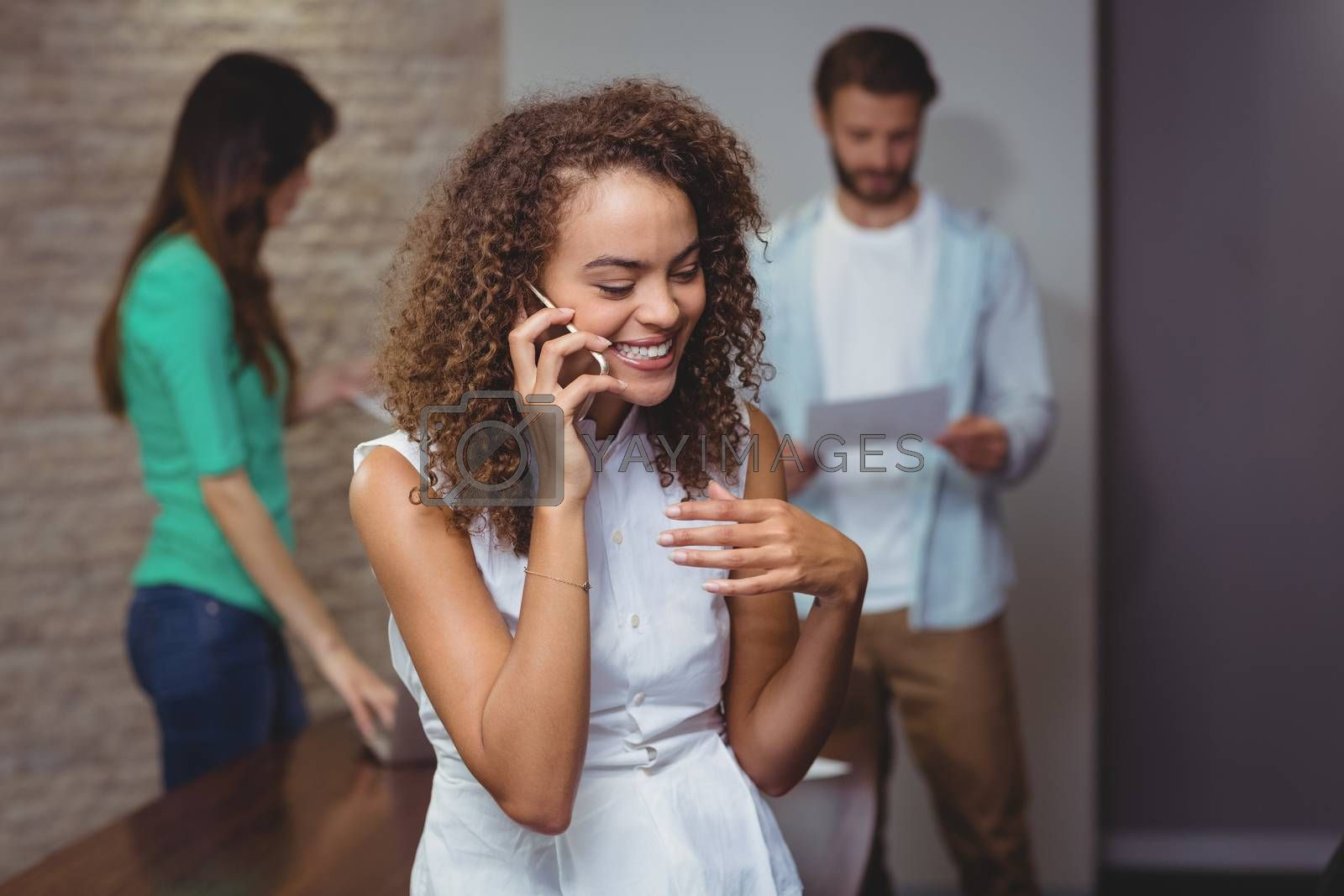 Smiling female executive talking on mobile phone in office