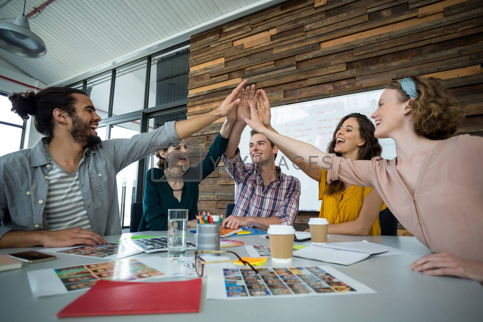 Happy graphic designers giving high five during meeting in office