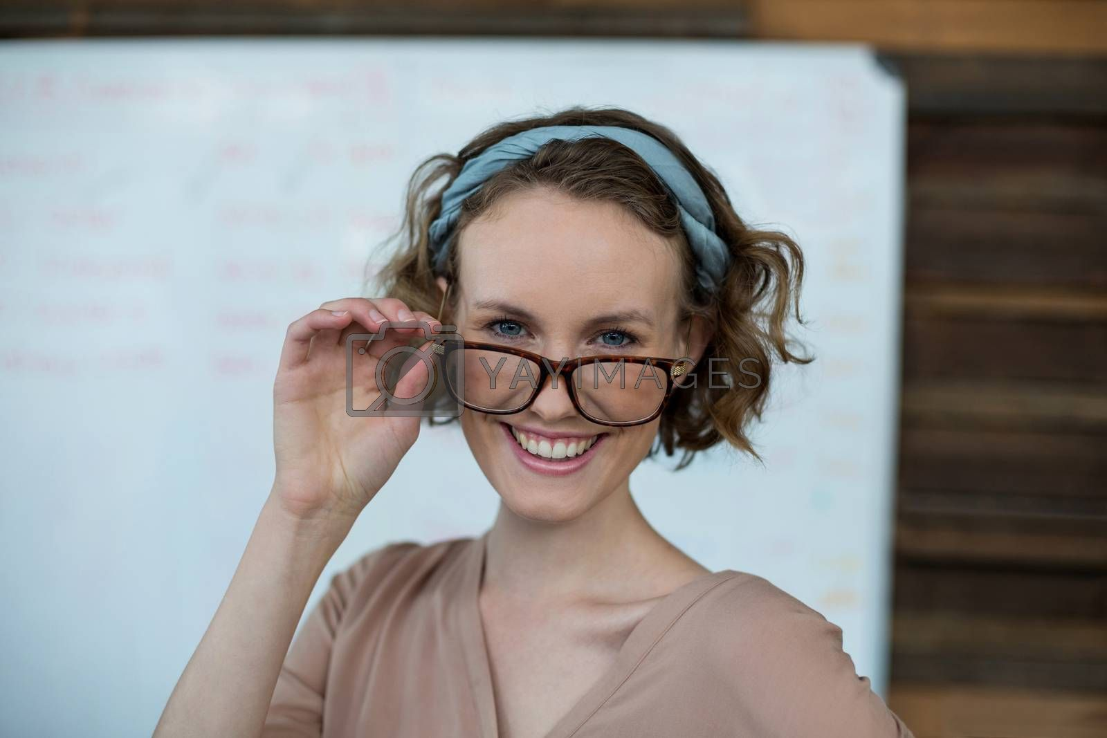 Portrait of smiling female executive holding spectacles in office