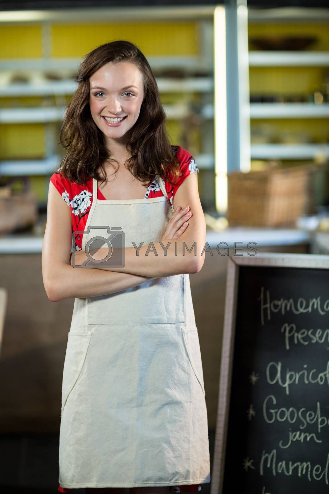 Portrait of a female shop assistant standing besides menu chalk board with her arms crossed