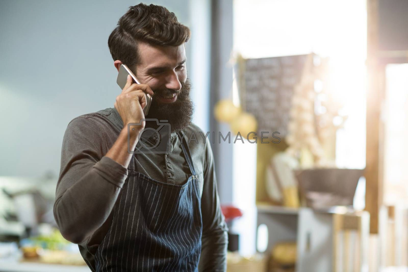 Salesman talking on mobile phone at counter in grocery shop