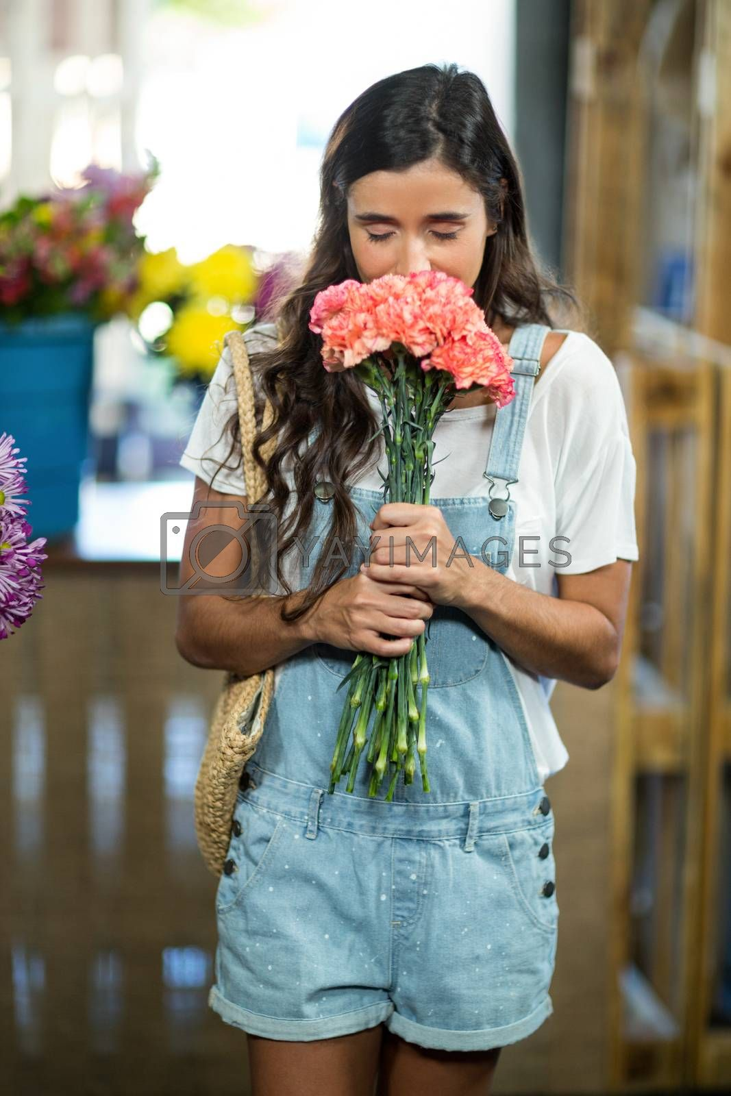 Woman smelling a bunch of flowers at florist shop