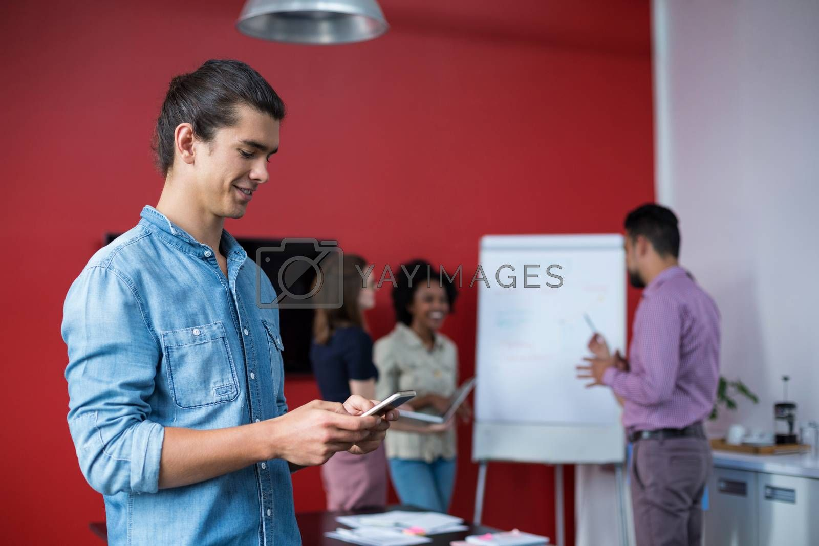 Business executive using mobile phone at meeting in office
