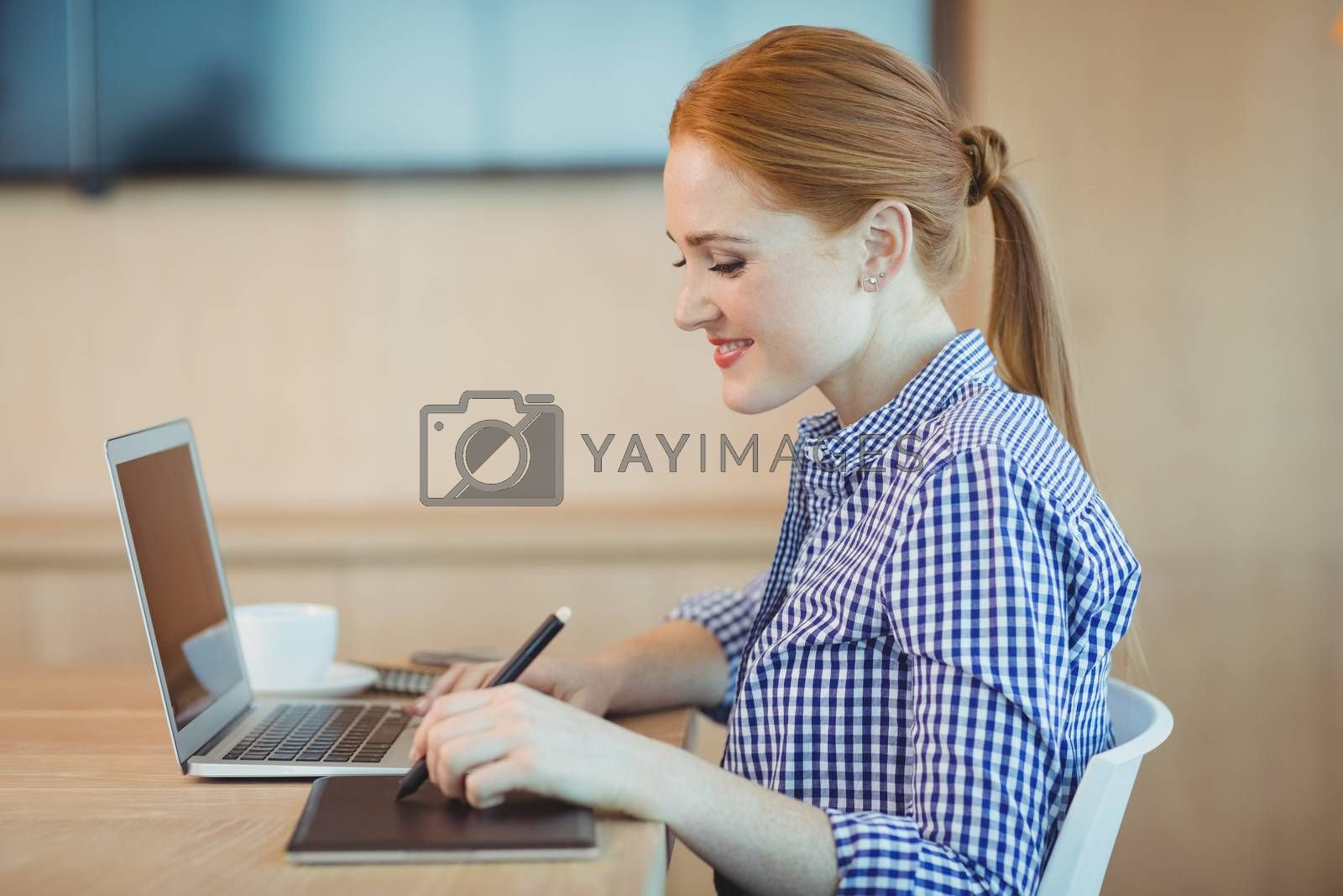 Female graphic designer using graphics tablet in office
