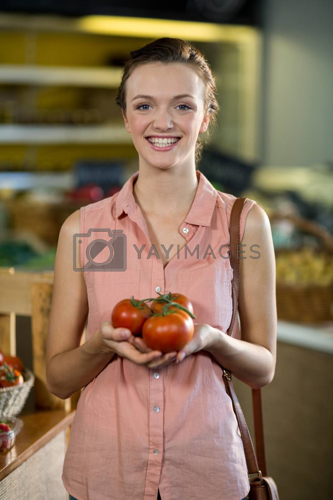 Smiling woman holding tomatoes in the grocery store