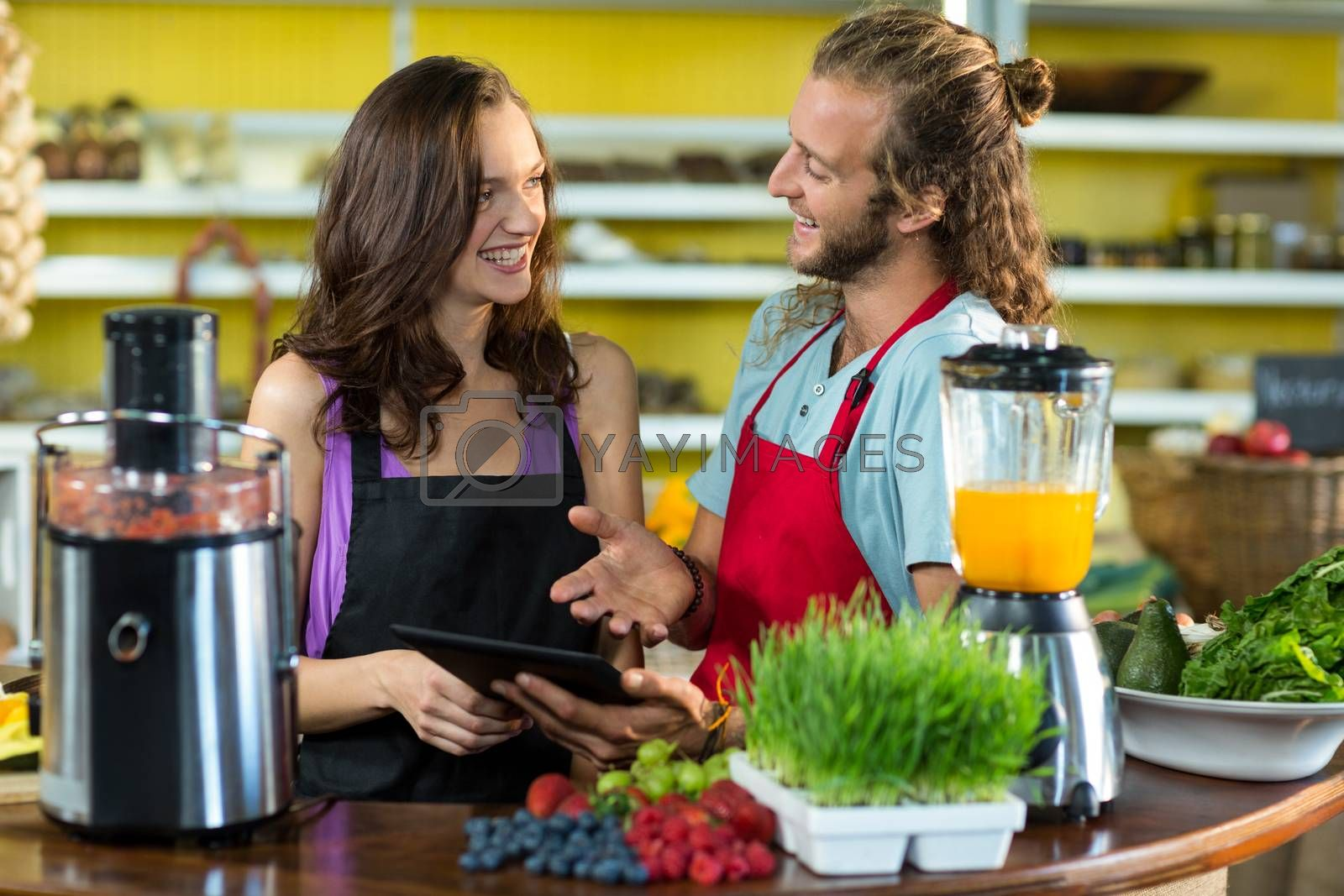 Smiling shop assistants discussing with digital tablet at health grocery shop