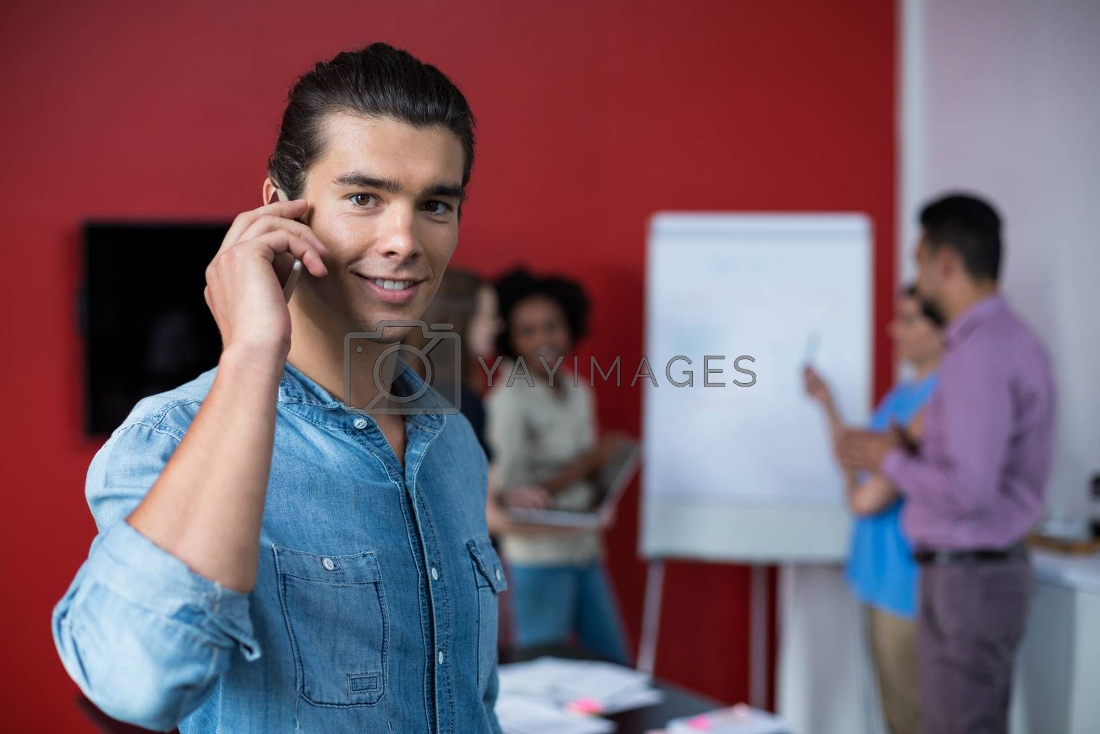 Business executive talking on mobile phone at meeting in office