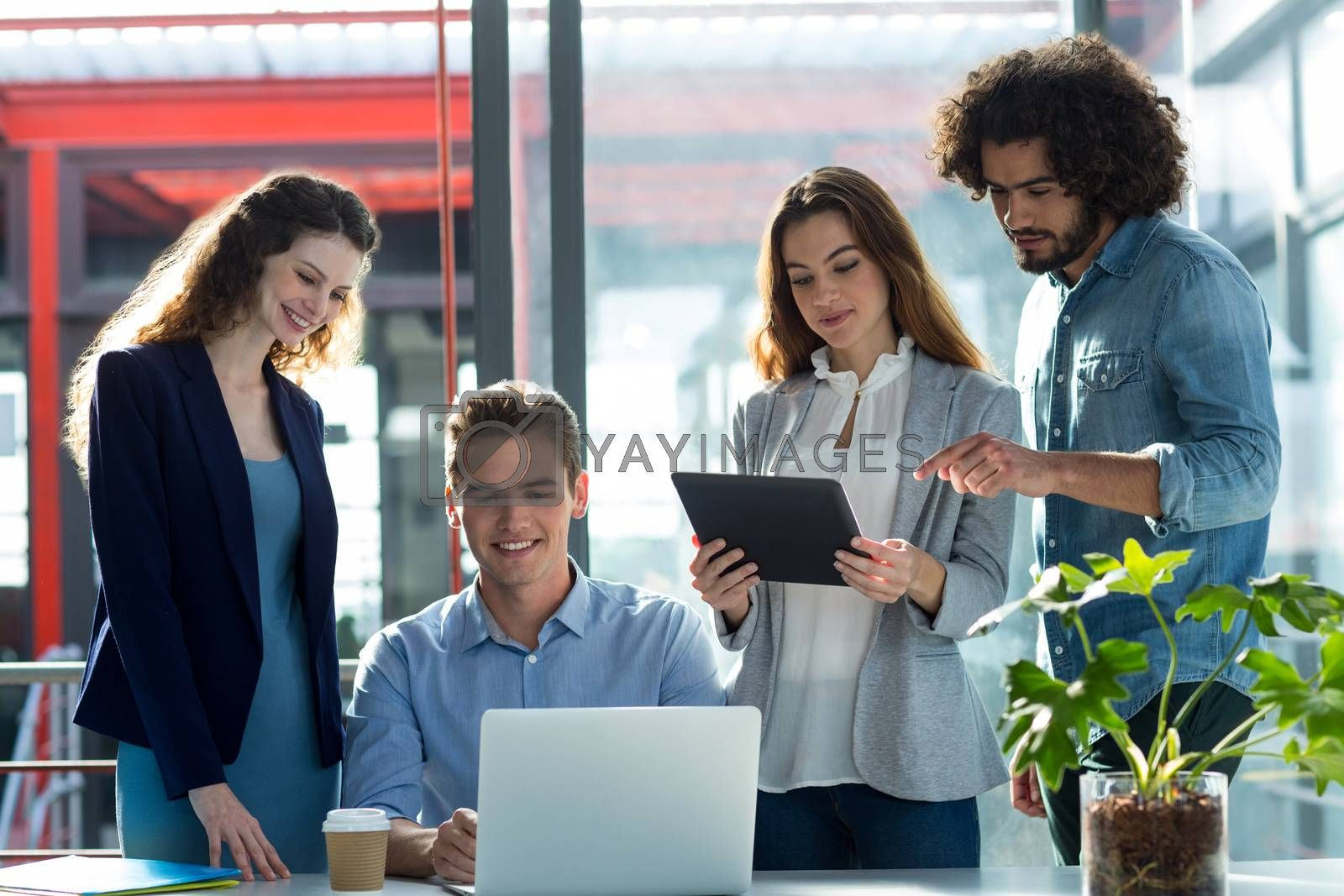 Businesspeople having discussion over laptop and digital tablet in office
