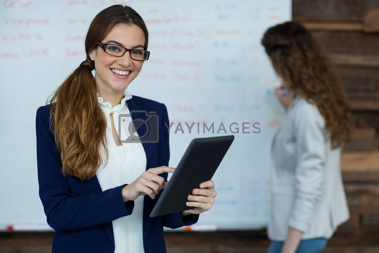 Portrait of smiling businesswoman using digital tablet in office