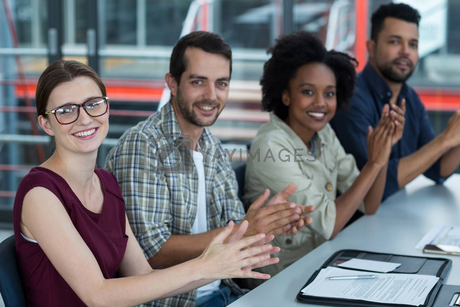 Portrait of smiling business executives clapping in meeting at office