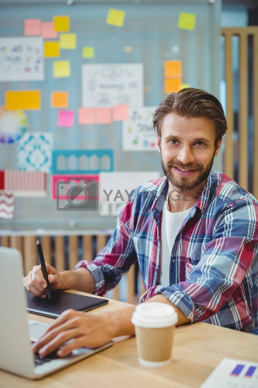 Portrait of happy graphic designer using laptop and graphic tablet in office