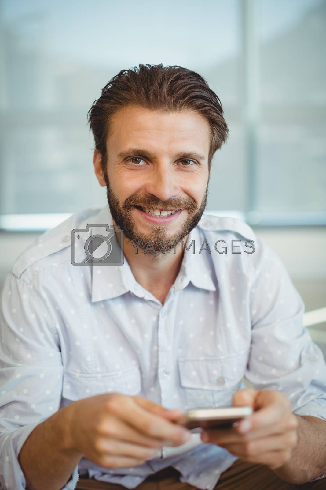 Portrait of male business executives using mobile phone in office