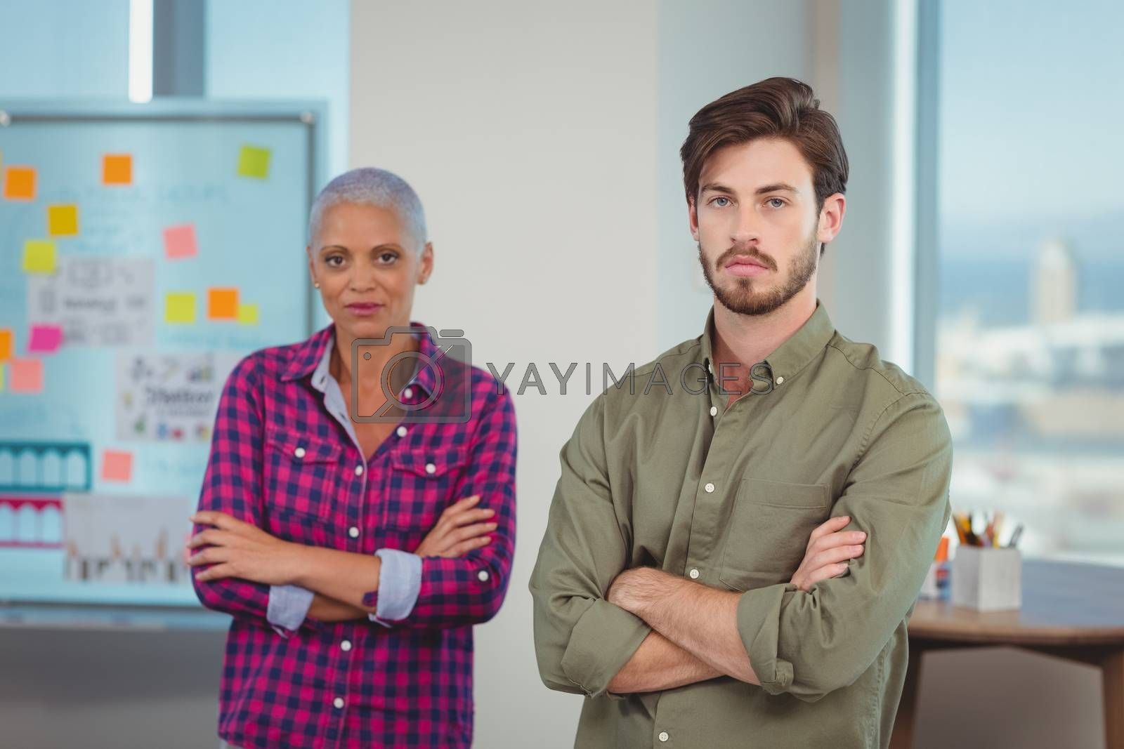 Portrait of business executives standing with arms crossed in office