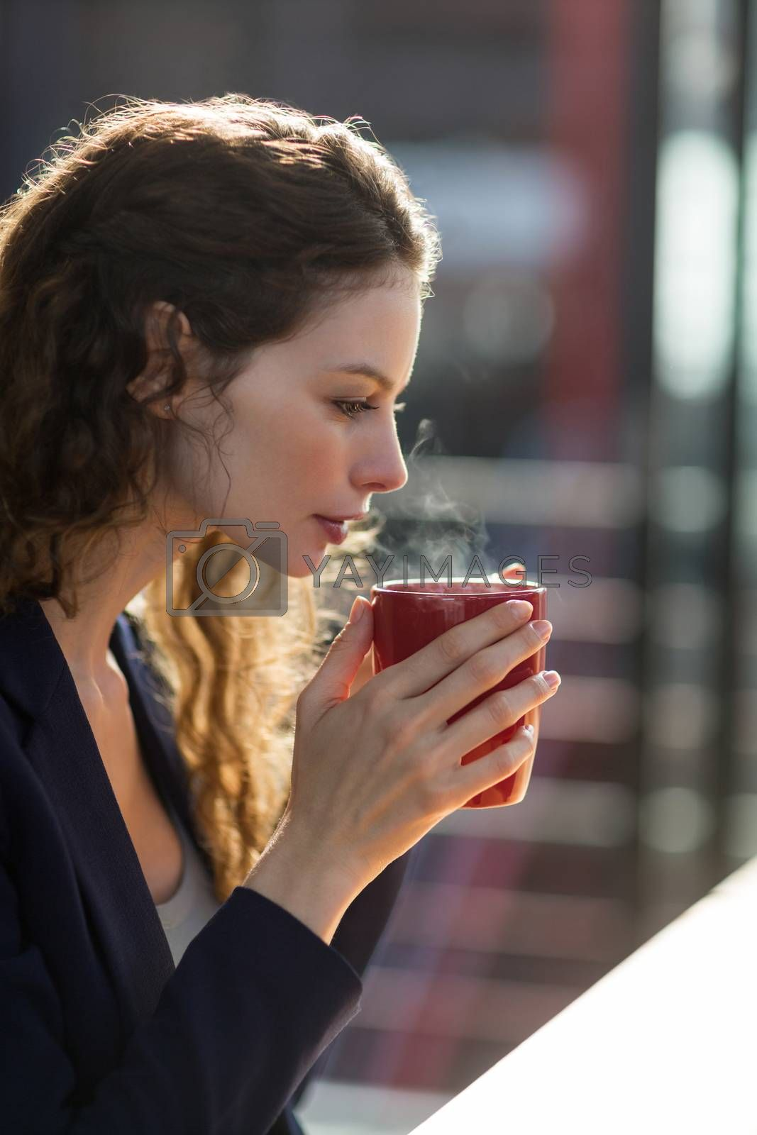 Beautiful businesswoman drinking cup of coffee in office