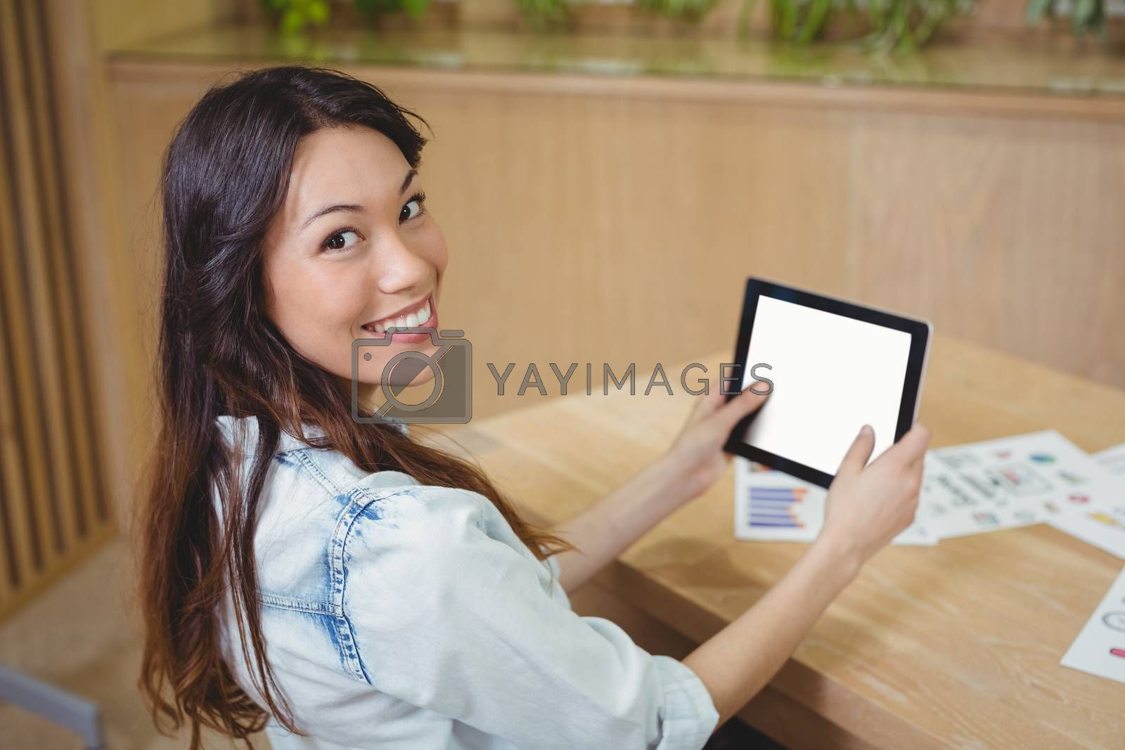 Portrait of female business executive using digital tablet at desk in office