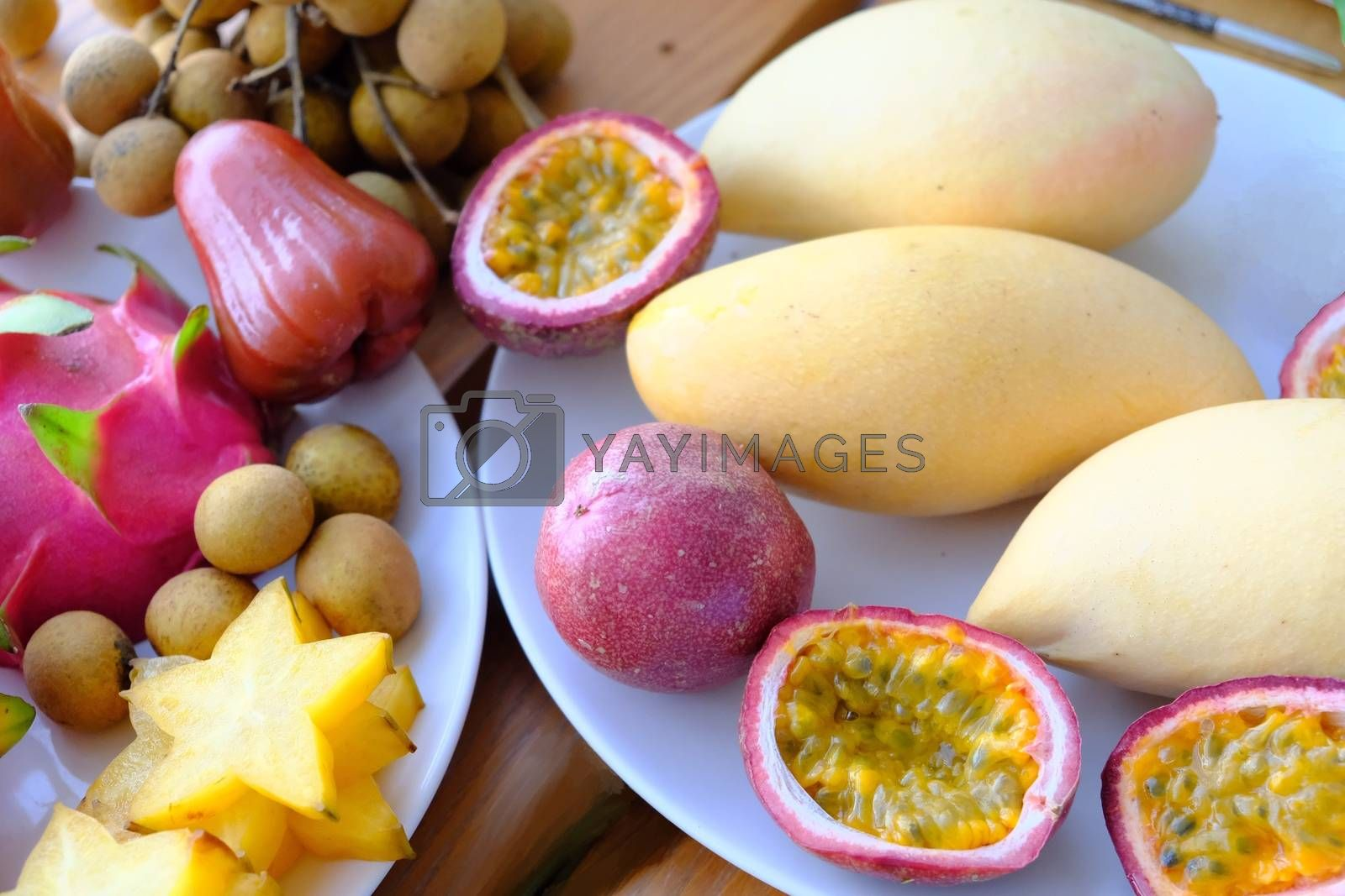 mix tropical fruits longan, mango, Rose apples, dragon fruit, Carambola and whole and cut passion fruits (maracuya) on the plate.