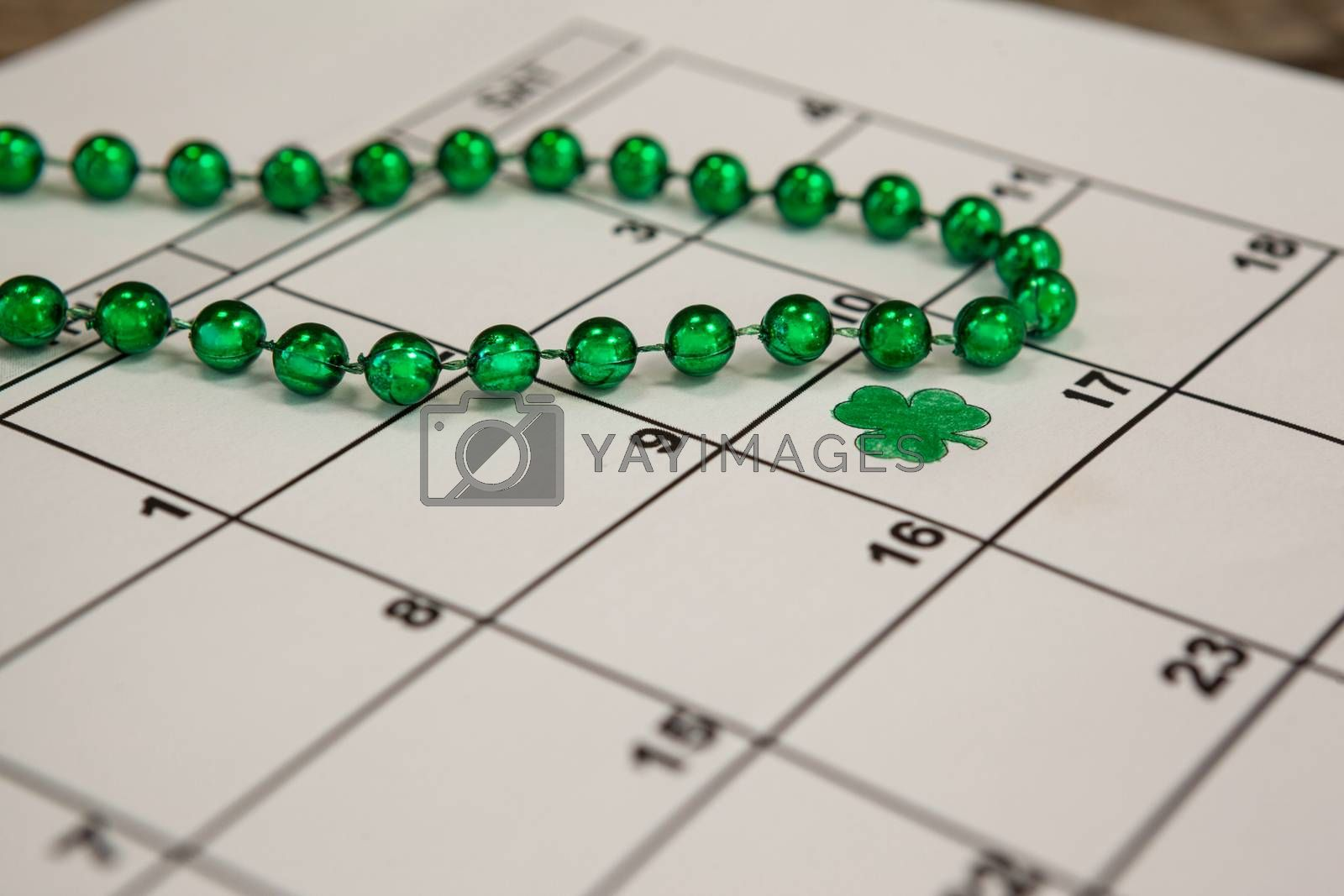 St. Patricks Day close-up of shamrock and beads kept on calendar