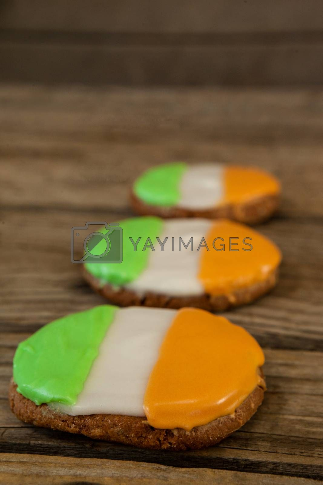 St. Patricks Day three cookies with irish flag toppings on wooden background