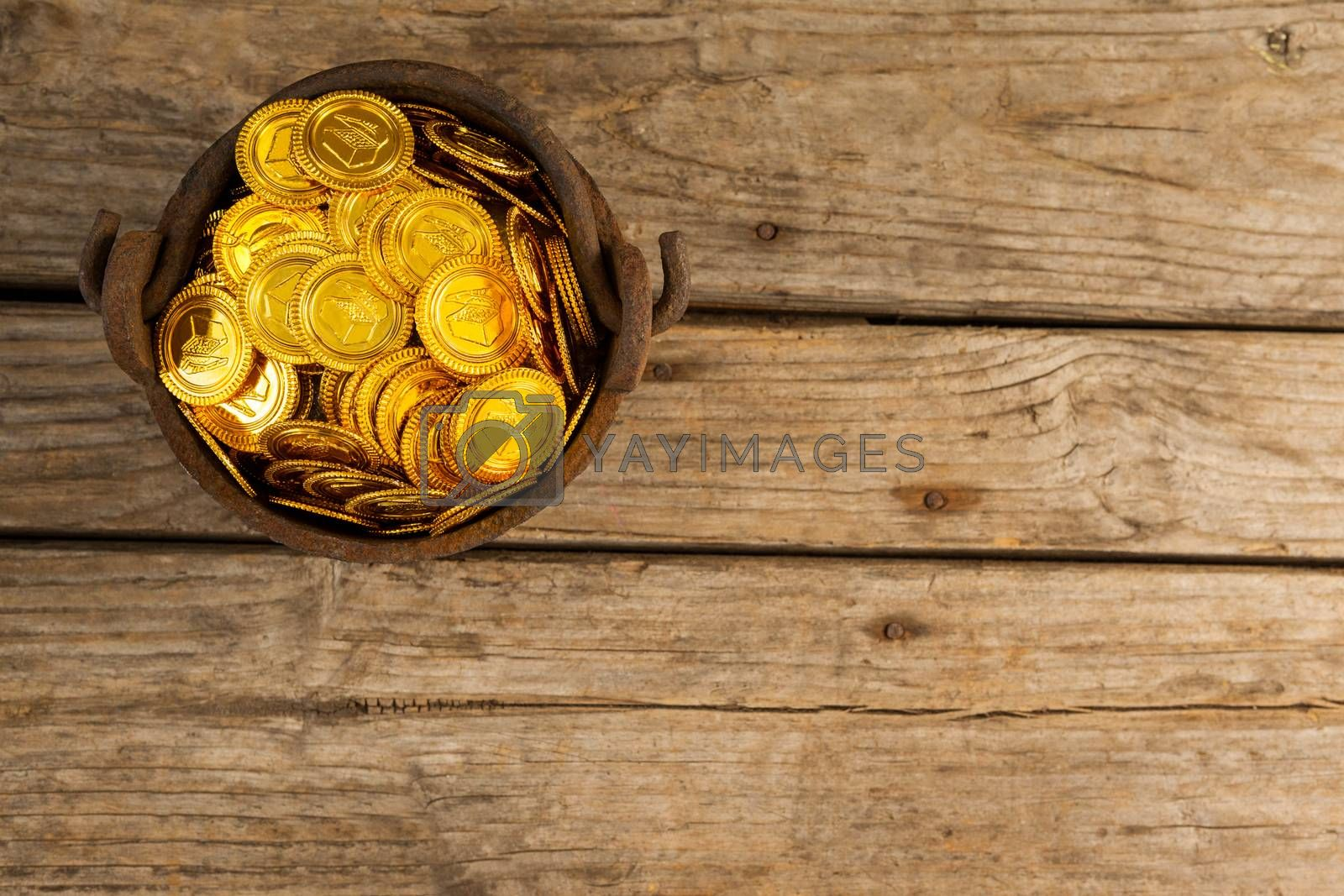 St. Patricks Day pot filled with chocolate gold coins on wooden background