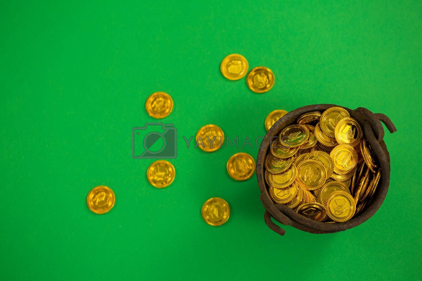St. Patricks Day pot filled with chocolate gold coins on green background